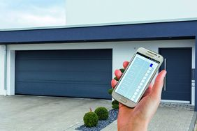 Hand mit Smart-Home-App vor Garage